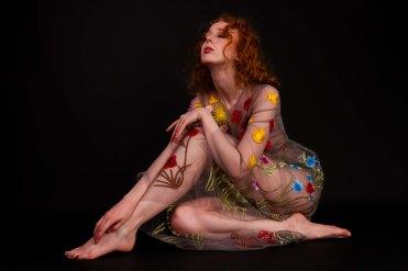 Gemma sat in a studio wearing a floral dress