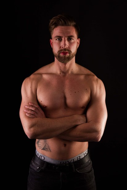 Topless male model in low key lit studio with black backdrop folding his arms