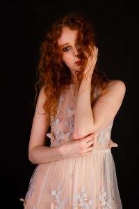 Red head model in sheer floaty butterfly dress in studio