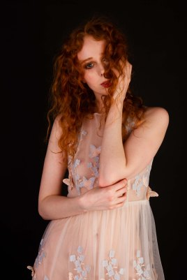 Red head model in sheer floaty butterfly dress in studio