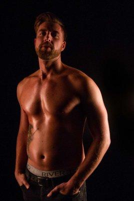 Male model in low light studio topless