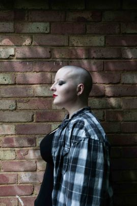 Side profile of bald model against a brick wall with flickers of light