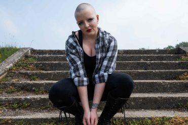 Bald model knelt in front of steps