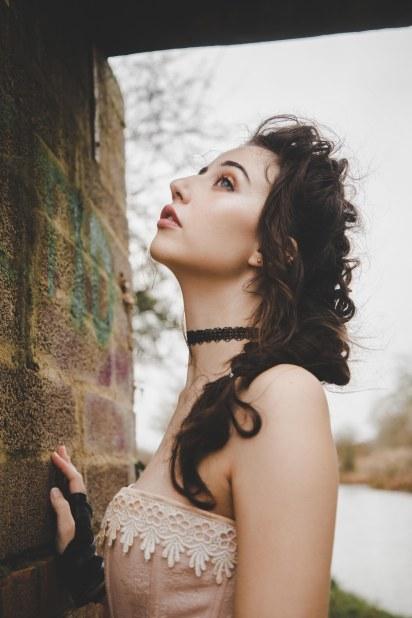 Brunette model side portrait with brick backdrop