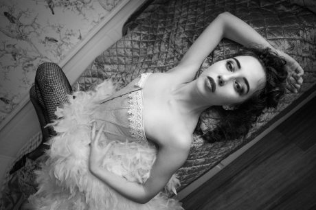 Black and white portrait of model laying across the bed