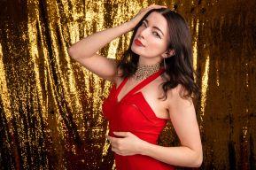 Brunette model portrait in red dress with glitter background