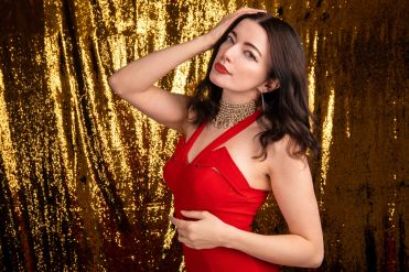 Brunette model portrait in red dress with glitter background