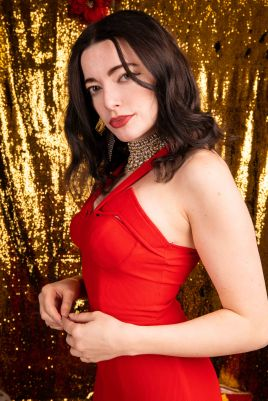 Portrait of model in a red dress side on in front of glitter backdrop