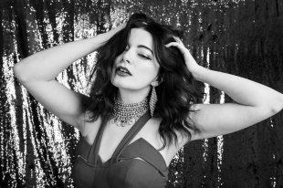 Portrait of model shaking her hair in front of glitter backdrop